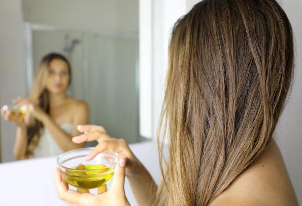 young woman applying an olive oil mask on hair in front of mirror scaled 1